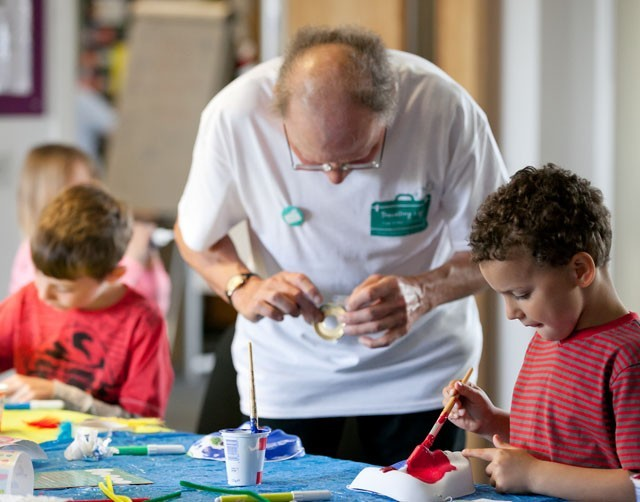 A man helping some children with a craft activity
