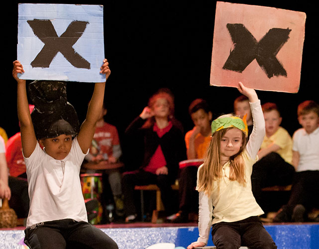 Two children hold an 'X' above their heads