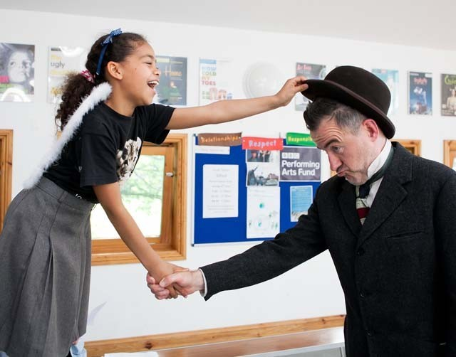 A girl shaking hands with a man while putting on his hat