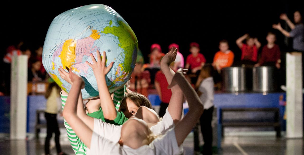 Children pass a blow up globe down a line