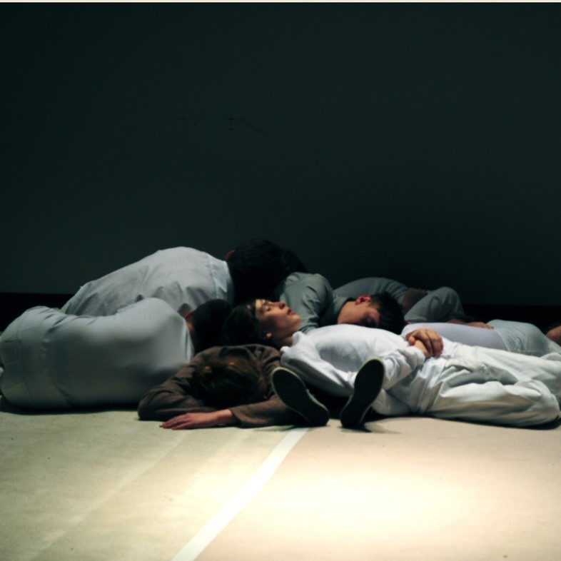 Bodies lay on the floor of a white space