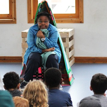 Actor, Corinne Walker, performs in front of an audience of local young people