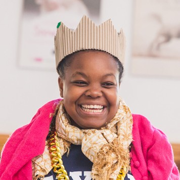 A performer, Corinne Walker, in a crown, beaming