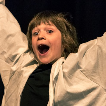 Pupil performs as an excited scientist during Play In A Week 2018